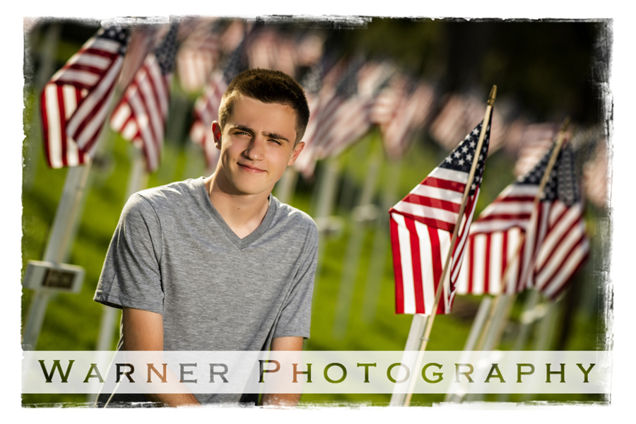 On location senior portrait of Andrew in Downtown Midland by the Tridge with American flags