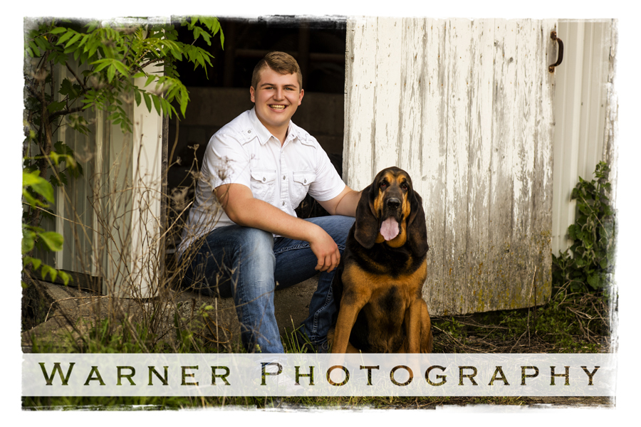 Senior portrait of Keegan in front of a barn with his dog on location at his farm.