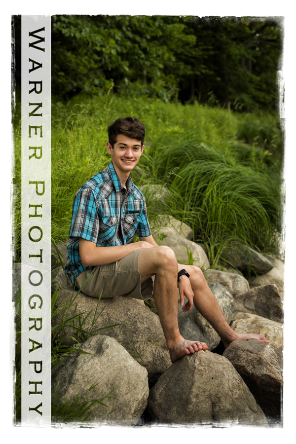 Senior portrait of Jeremy on the rocks at Chippewa Nature Center