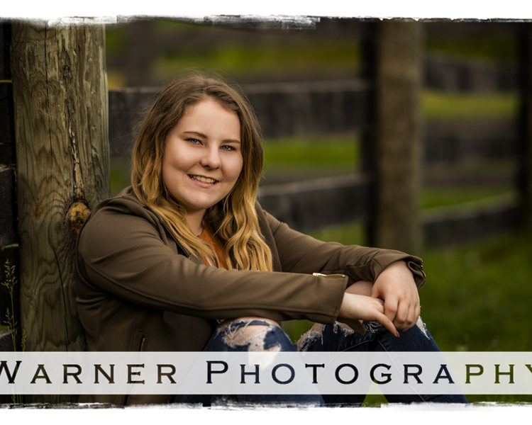 Senior portrait of Jessica by a rustic fence at Chippewa Nature Center in Midland Michigan