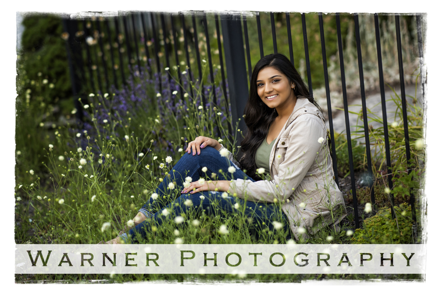 Senior portrait of Disha, a Standish Sterling High School senior, taken in Downtown Bay City by a fence with flowers.