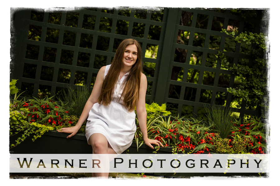 A senior portrait of Midland High School senior Hailey at Dow Gardens with reds and greens
