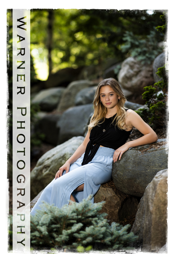 A portrait of Dow High School Senior Isabella at Dow Gardens on the rocks
