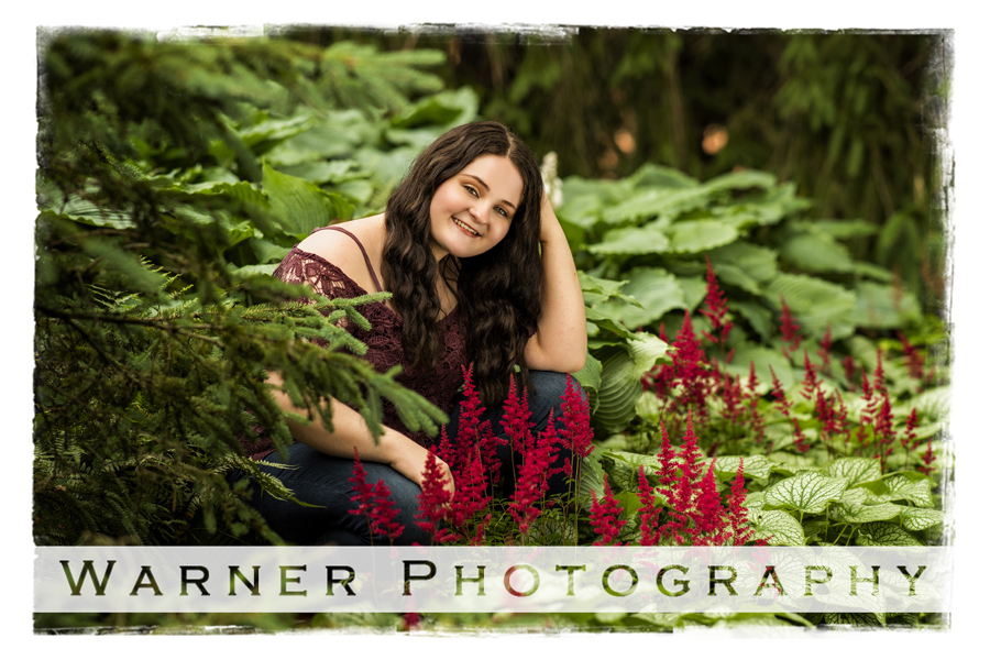 A senior portrait of Bay City Western senior Kristina at Dow Gardens with green leaves and red flowers