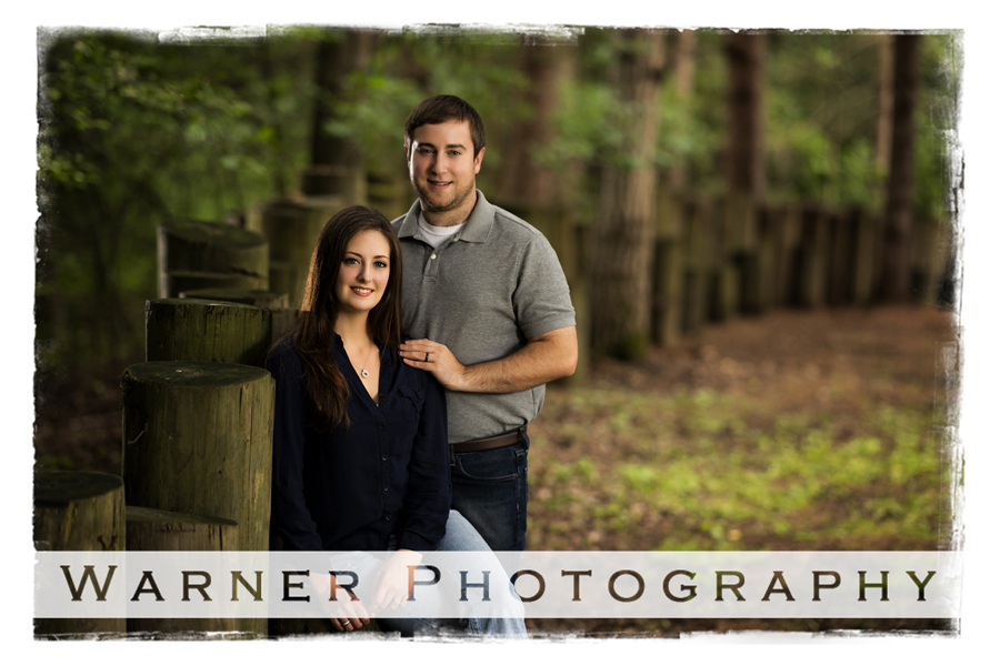 A portrait of Amy and Craig on their wooded property by a wooden fence post