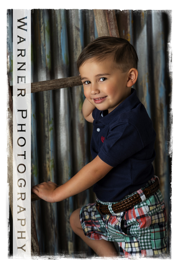 A Back to School portrait of Anson at the Warner Photography Studio next to a wooden ladder with a metal backdrop