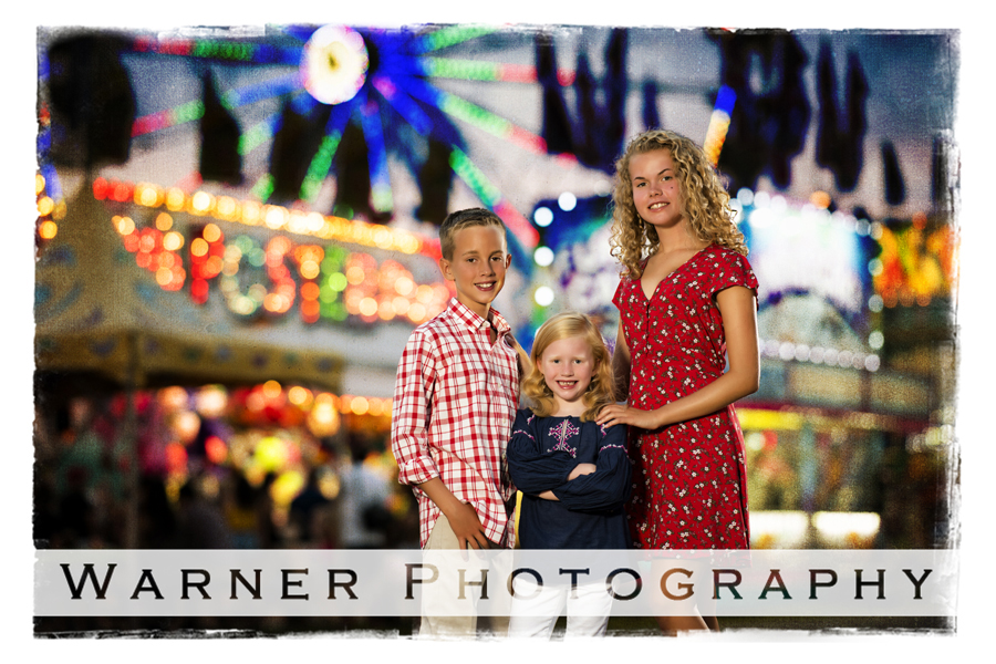Portrait of the Buckhave children at the Midland County Fair by the midway at dusk with fair lights