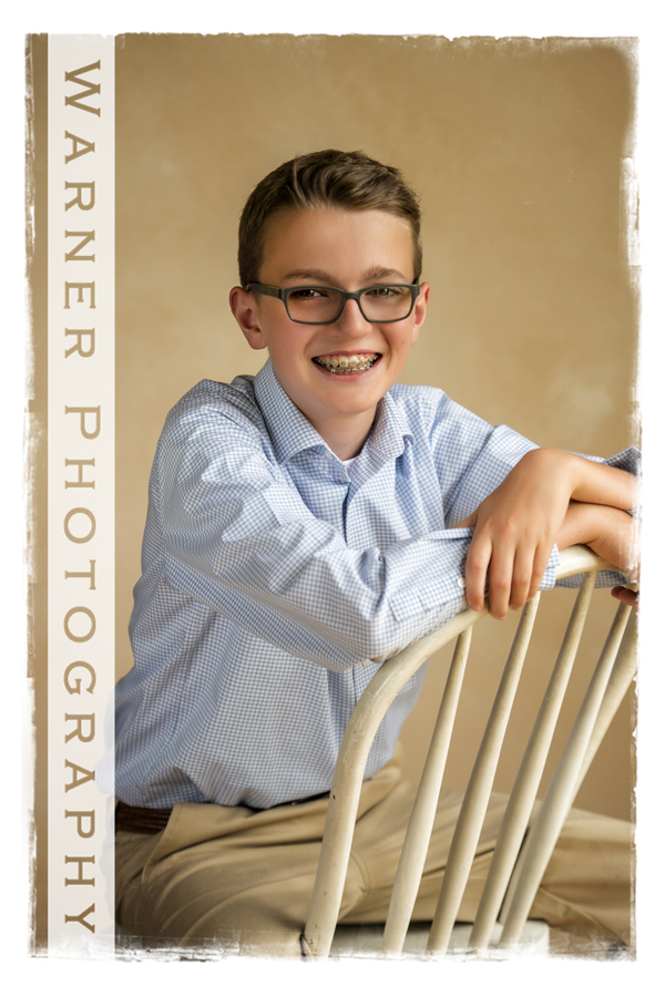 Warner Photography studio portrait of Flynn for his back to school portrait sitting on a chair