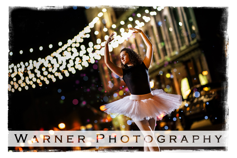 A portrait of Midland High School senior Hadley in Downtown Bay City by the bridge of lights in her leotard and tutu at night