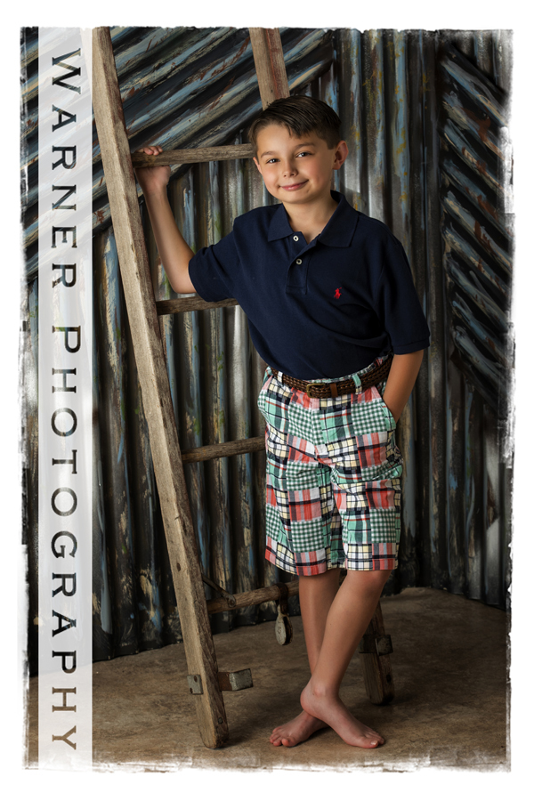Back to School portrait of Ian at the Warner Photography Studio with a ladder propped against a metal background
