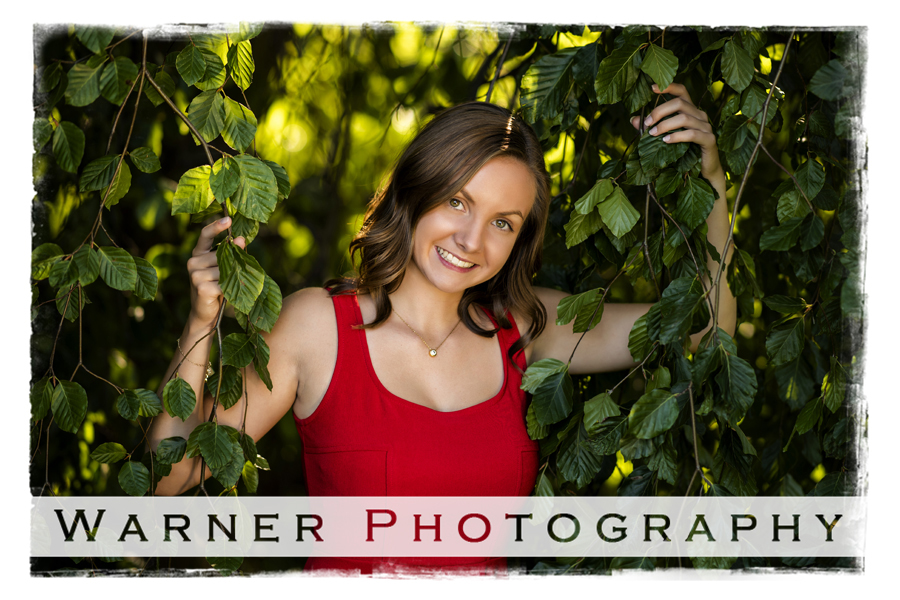 A senior portrait of Hemlock High School senior Madison at Dow Gardens in Midland Michgan surrounded by green leaves
