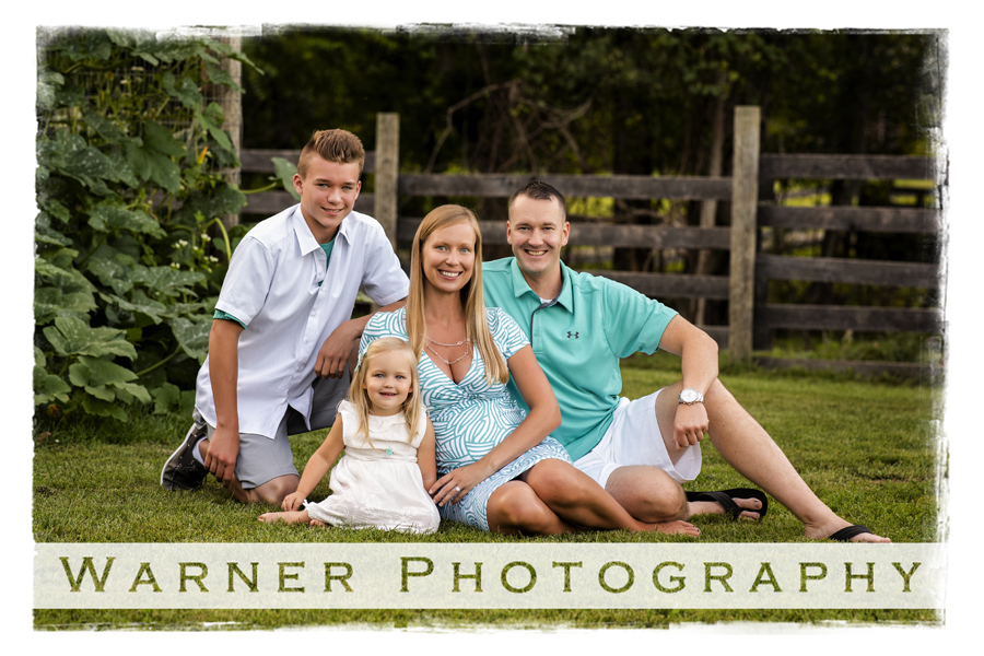 An outdoor portrait of the Peeler family at Chippewa Nature Center by a wooden fence