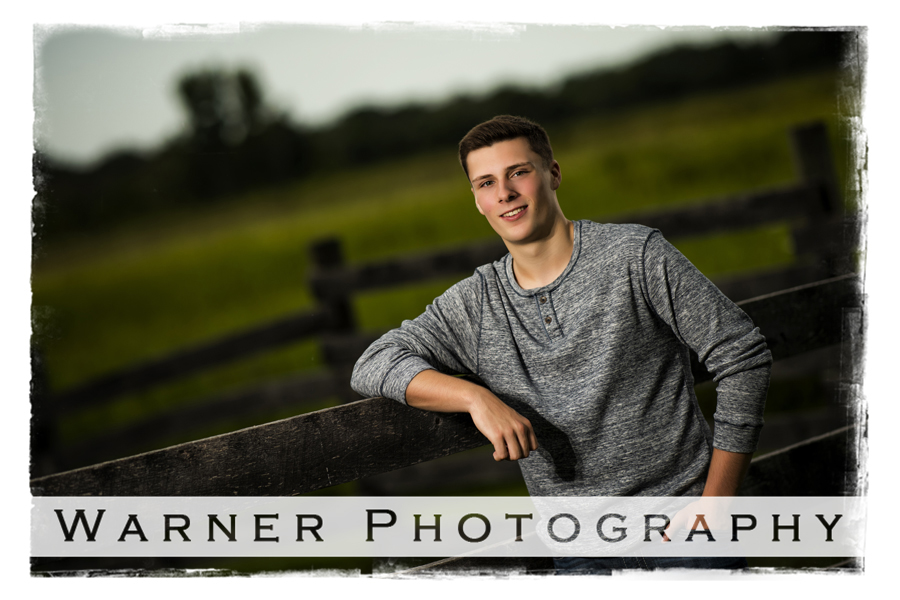 Portrait of Bullock Creek High School senior Zach at Chippewa Nature Center in Midland Michigan by an old wooden fence