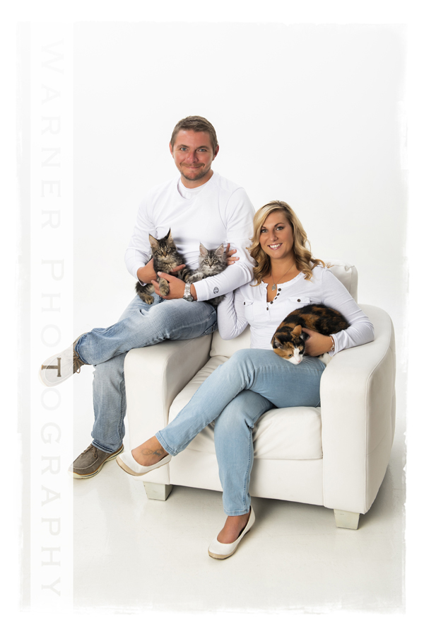 Classic family portrait of Jennifer and Luke at the studio in a white chair with their cats
