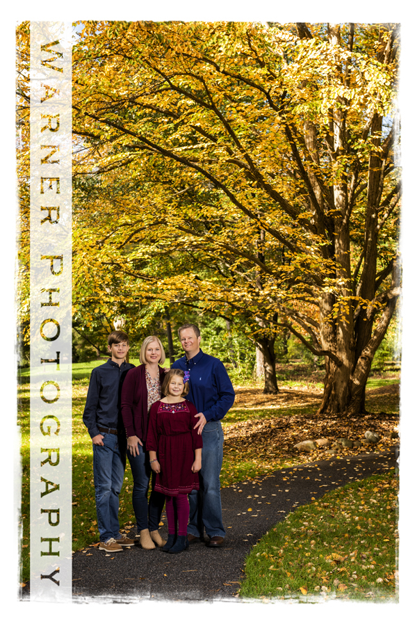 An outdoor family portrait of the Frame family at Dow Gardens in midland michigan with yellow fall trees