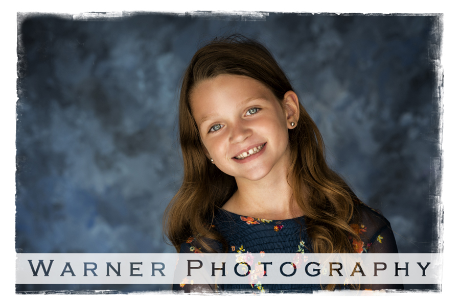 A traditional Back to School portrait of Grace at the Warner Photography studio with a blue background
