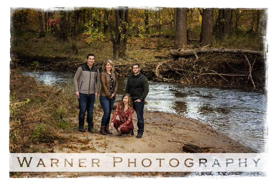 A fall family portrait on private property of the Hopkins family in the woods near a stream of water