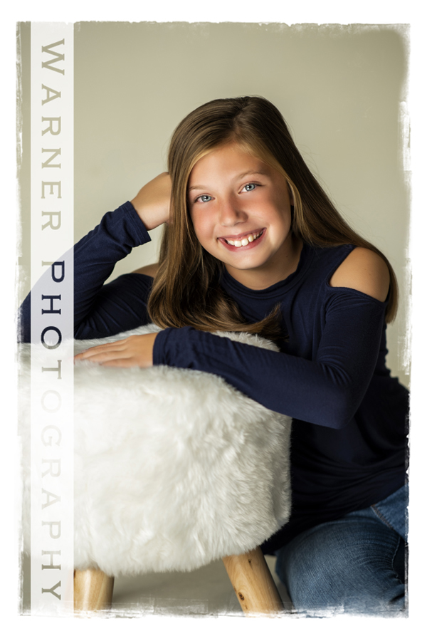 A Back to School portrait of Jensyn at the Warner Photography Studio with a white fluffy stool