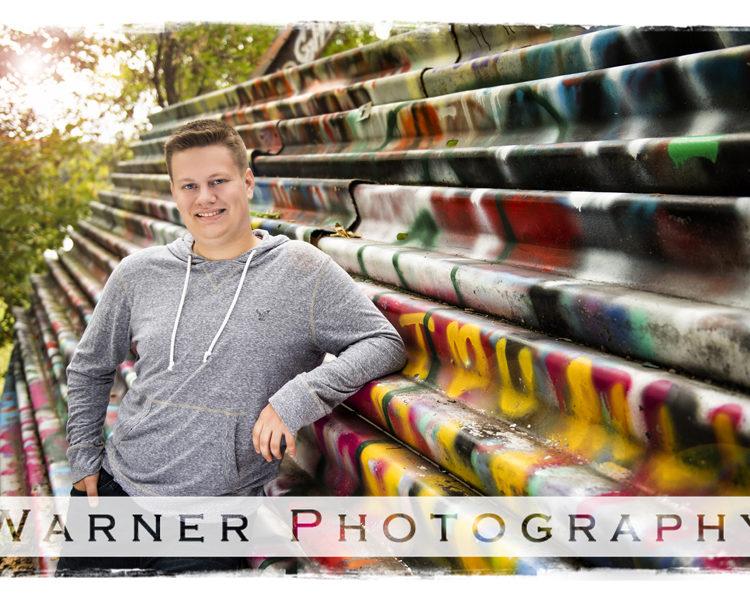 Senior portrait of Dow High School Senior Nicholas at the Bailey Bridge in Midland Michigan by the railling with graffiti