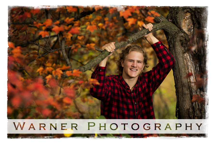 an outdoor senior portriat of Midland High School senior Sam at Chippewa Nature Center with the orange fall leaves