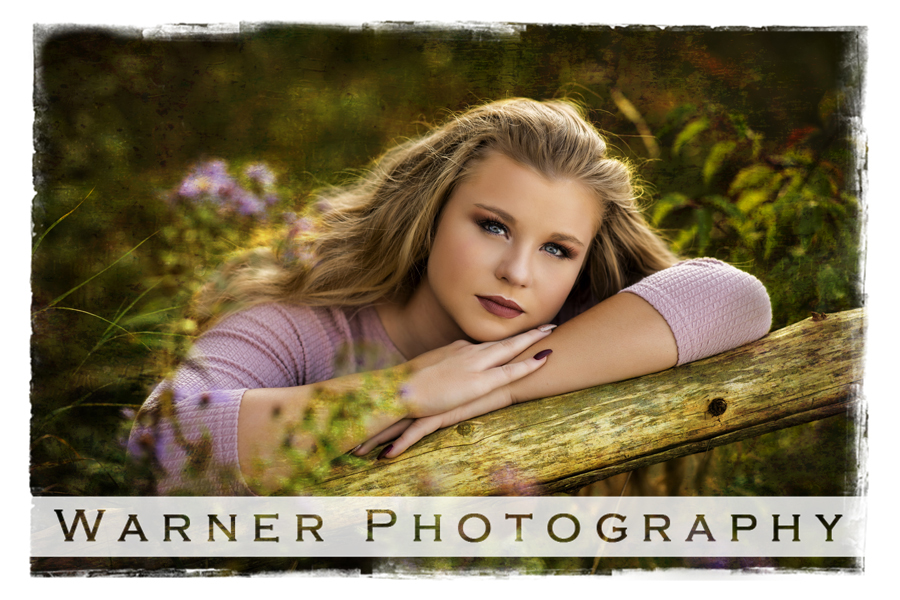 Outdoor senior portrait of Dow High School senior Sydney at Chippewa Nature Center on a wooden fence surrounded by wild flowers