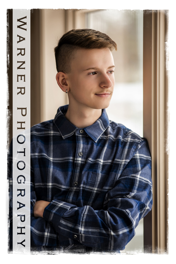 Traditional senior portrait of Dow High School senior Chad by the window at Warner Photography studio