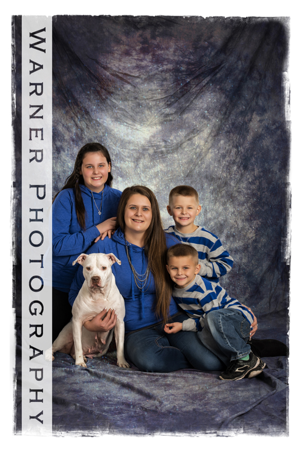 A classic family portrait of the Morr family and their dog at the Warner Photography Studio
