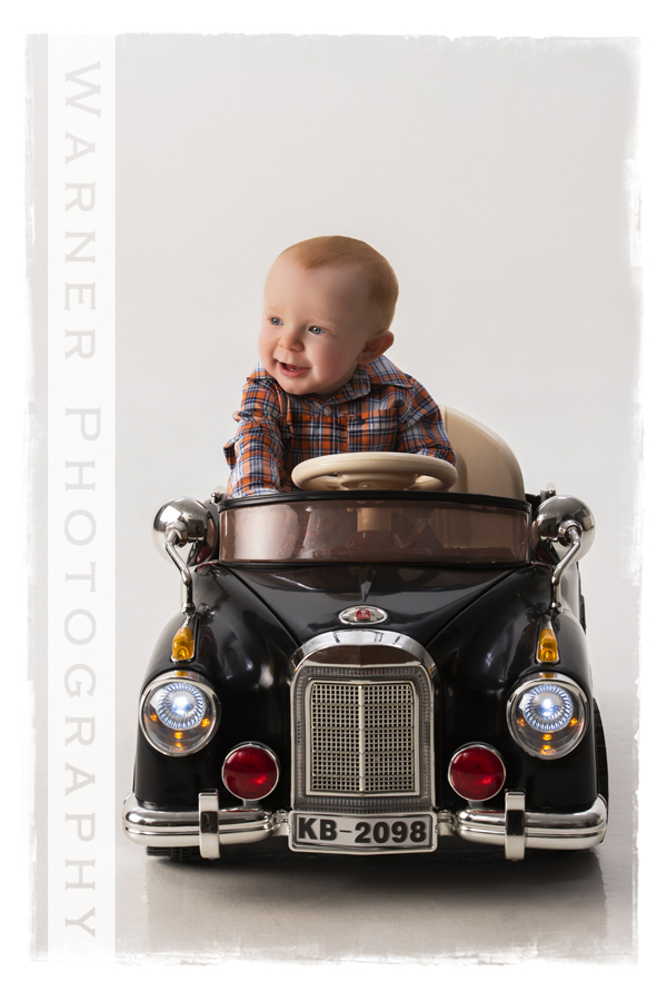 Classic year of memories portrait of Hudson for his 9 month session in his toy car at Warner Photography