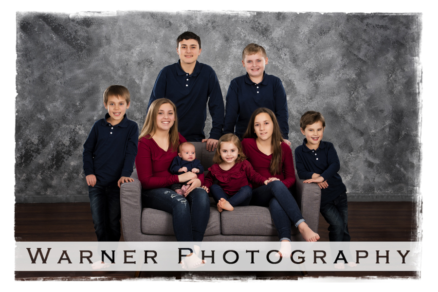 The Kreh Grandchildren at the Warner Photography Studio on a grey couch with a traditional grey background