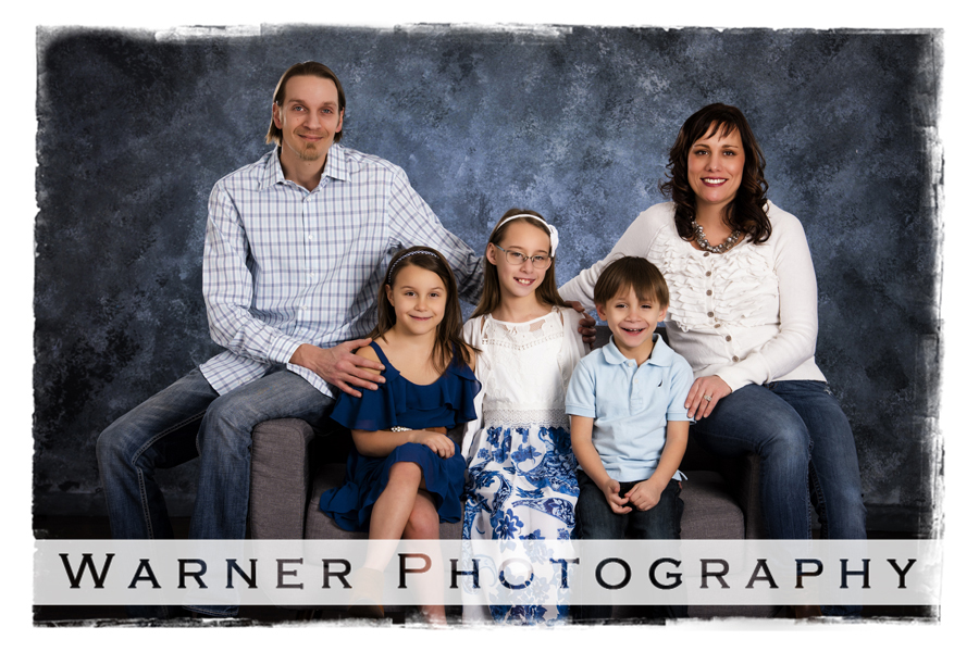 family portrait Losey family Warner Photography Studio seated on a grey couch with blue backgrounds