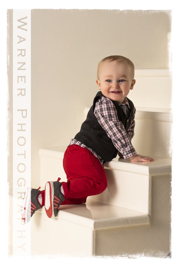 Childrens portrait of Keygan on white steps crawling red pants