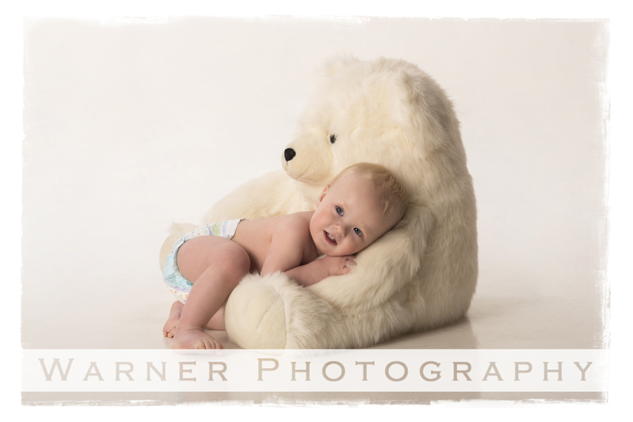 Childrens studio portrait of Amadeaus for his first birthday with a white bear and white background
