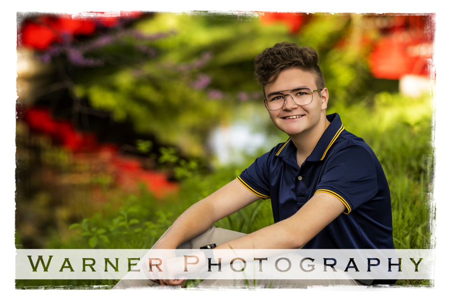 Outdoor senior portrait Dow Gardens red flowers midland high school senior Jacob