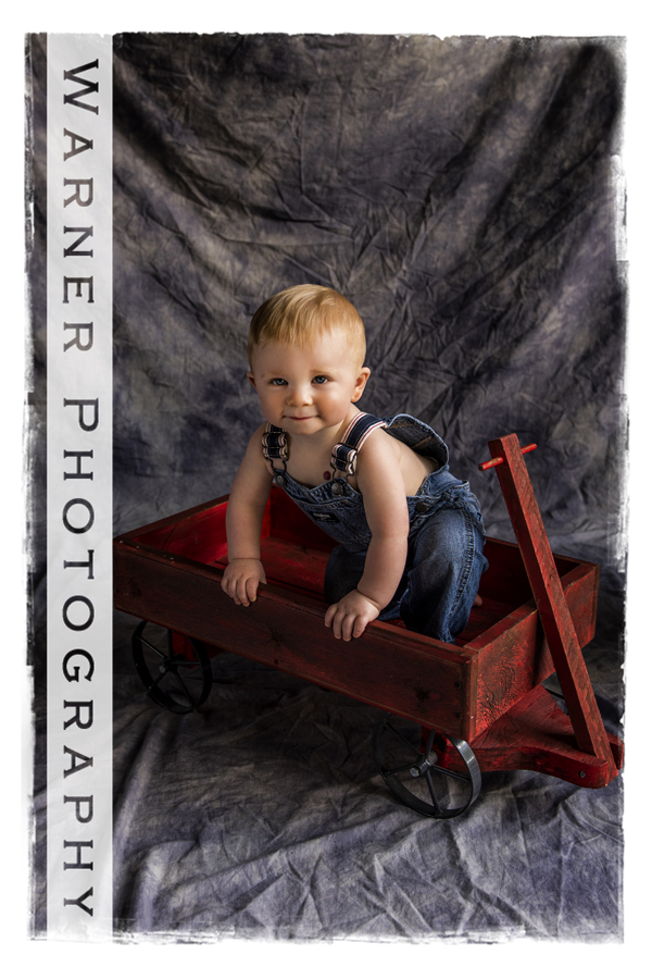 Studio childrens portrait of Wyatt in bib overals in a red wagon