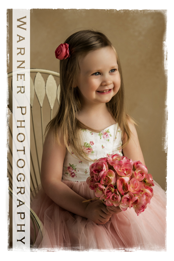 3rd Birthday pictue of Evie at the studio with pink roses and a white chair