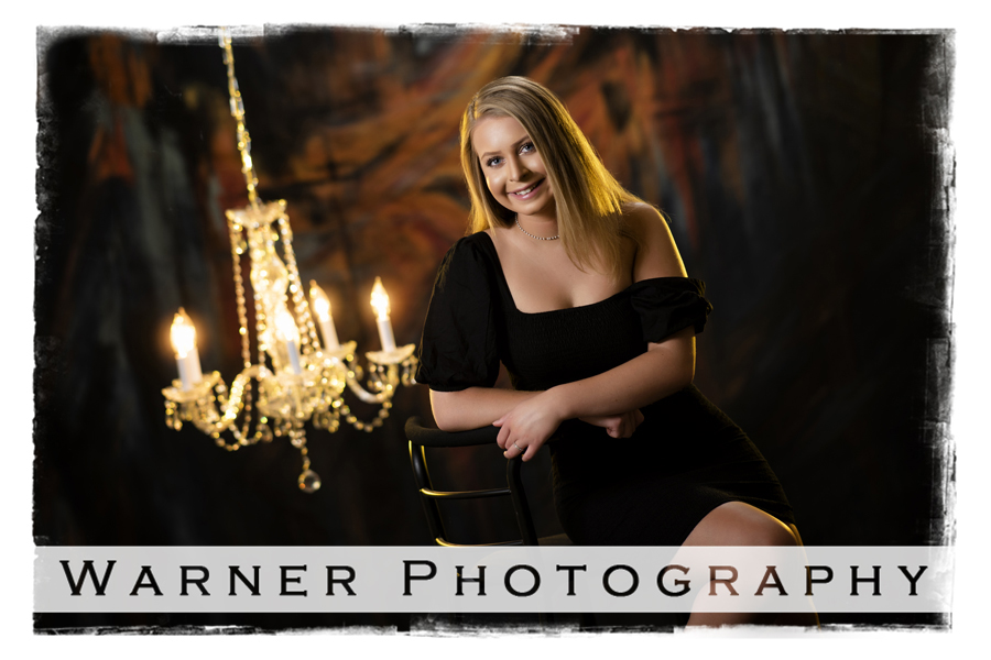 Studio senior portrait of Kayla with dark colors and a crystal chandelier