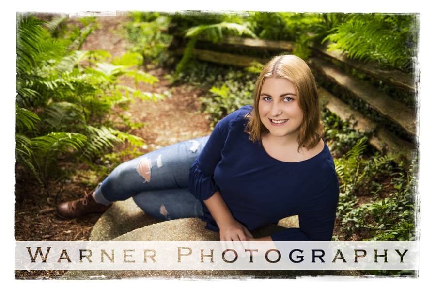 Outdoor portrait of Midland High School senior Danielle at Dow Gardens by a fence and greenery