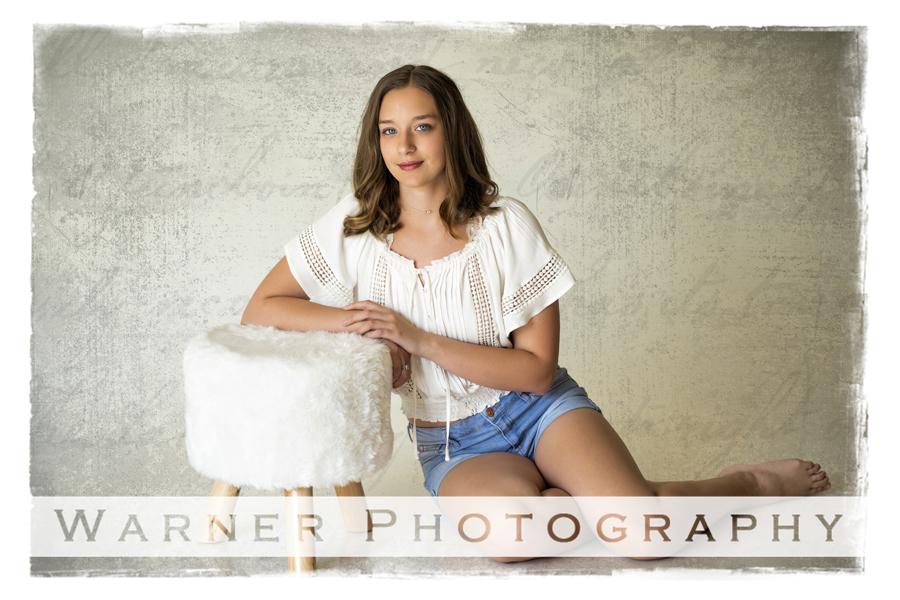 Studio portrait of Bullock Creek senior Lauren at the studio with a white stool