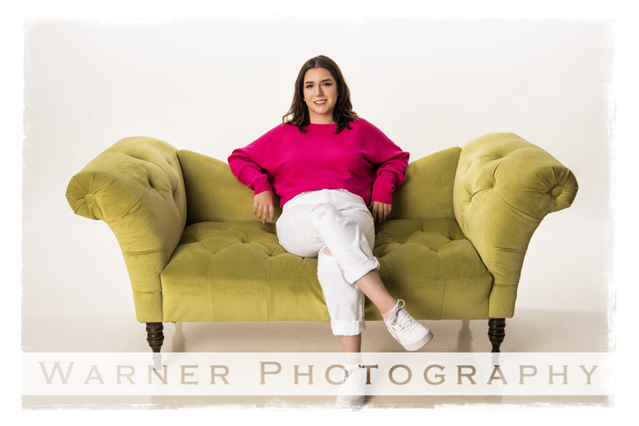 Studio portrait of Haily on a green couch at the Warner Photography Studiio