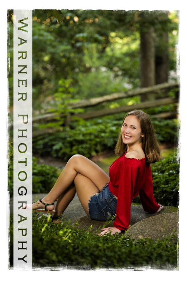 Outdoor senior portrait of Heritage High School senior Hayley at Dow Gardens by greenery and a wooden fence