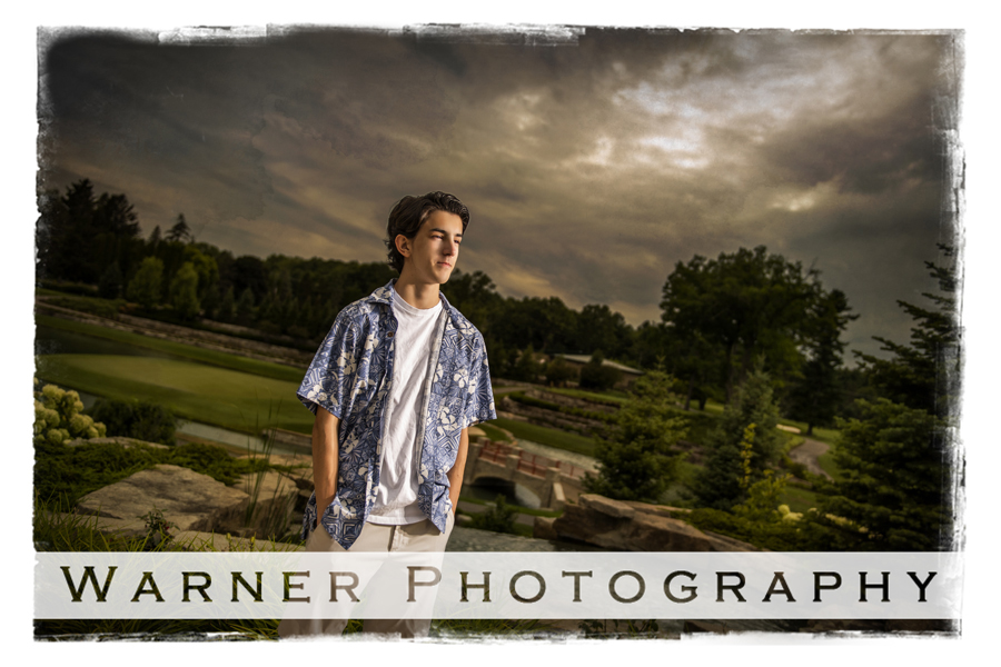 Outdoor portrait of Dow High senior Jeffery at the Midland Country Club with a dark sky and the golf course