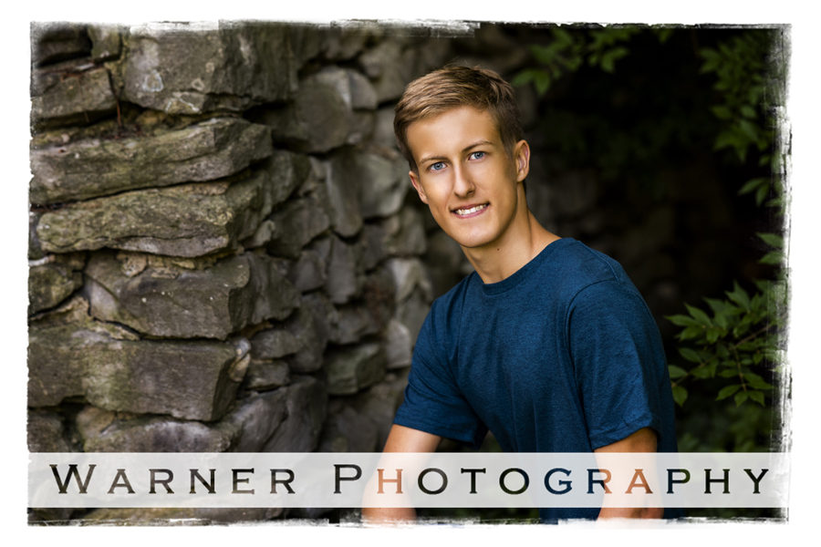Outdoor senior portrait of Dow High School senior Nathan at Dow Gardens with a rock wall