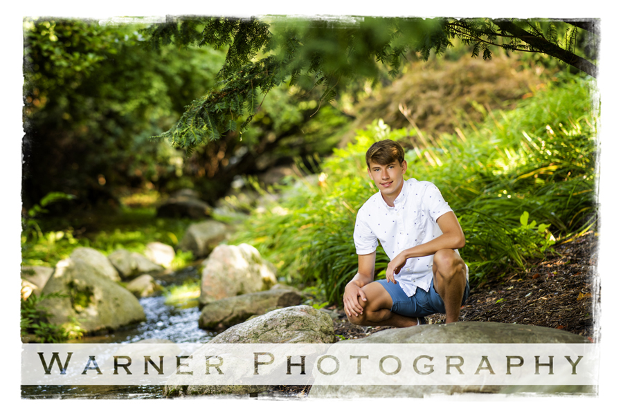 Outdoor senior portrait of Dow High School senior Drew at Dow Gardens by some rocks and a stream