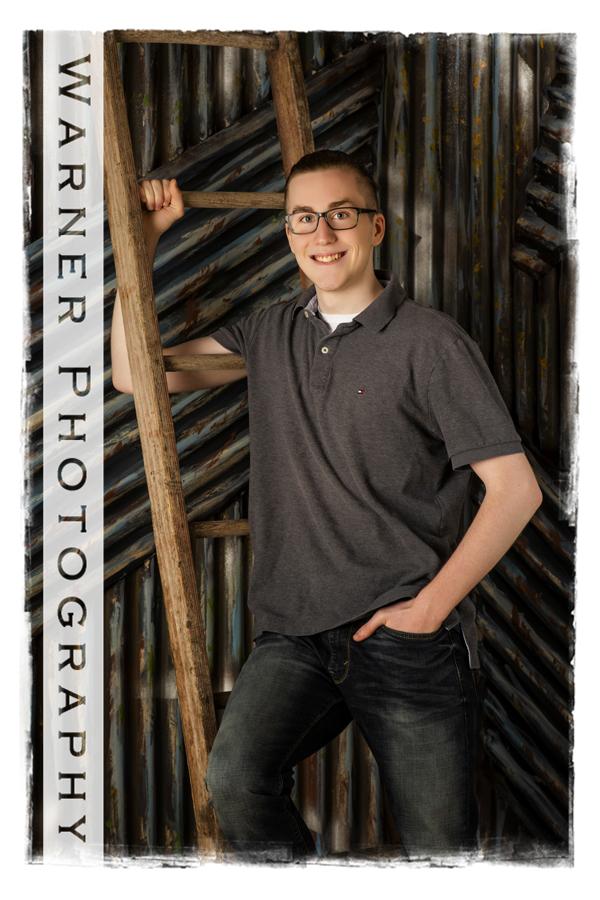 Studio portrait of Midland High School senior Josh by a ladder on a metal wall