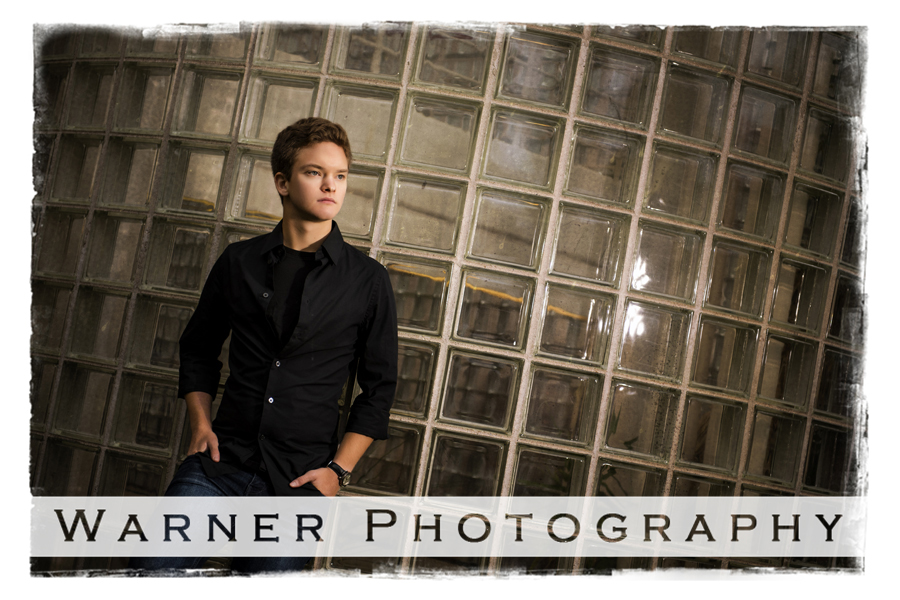 Outdoor senior portrait of Dow High School senior Marcus in Downtown Midland by a glass block wall