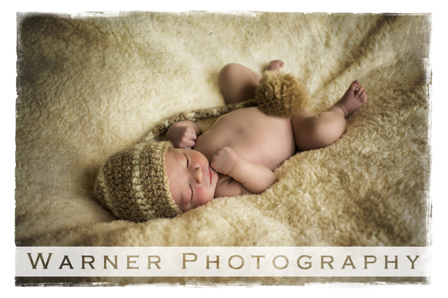 Studio portrait of newborn Oliver on a soft golden blanket with a long stocking cap