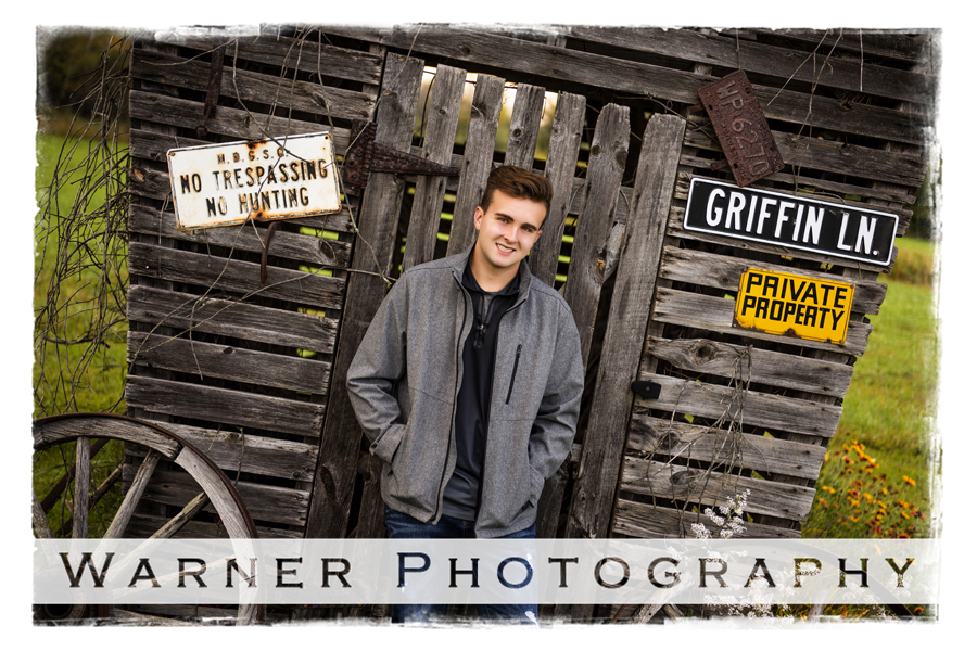 On location senior portrait of Ogemaw Heights senior Robby in front of a wooden shed on private property