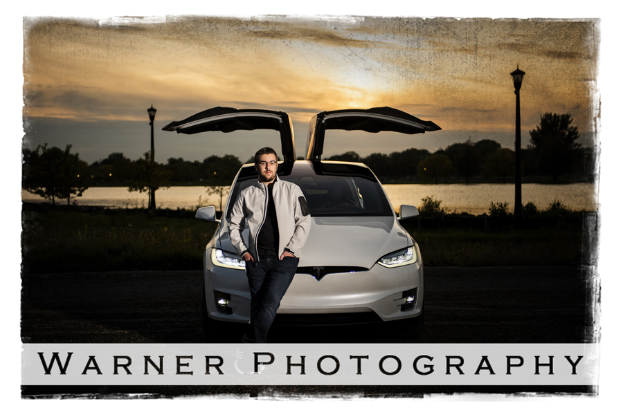 outdoor senior portrait of Coleman High School senior Bradley in Downtown Bay City with a sunset and a Tesla