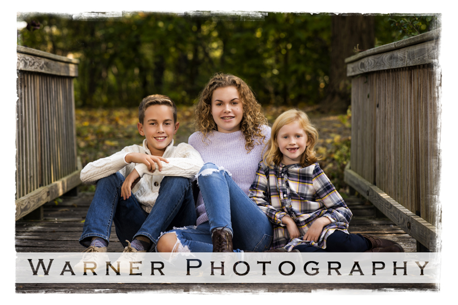 outdoor portrait of the Buckhave children at the Chippewa Nature Center on a wooden bridge