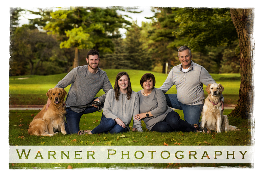 Outdoor family portrait of the Millhisler family with their dogs